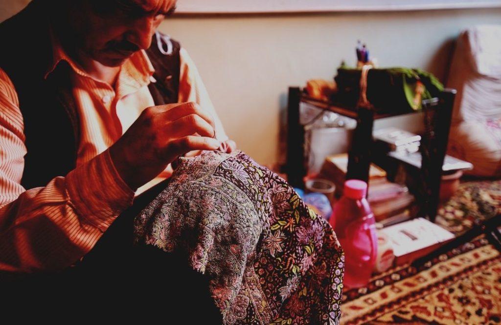 The Kashmiri Artisan hand embroidering an exquisite Pashmina Shawl in Sozni Kari